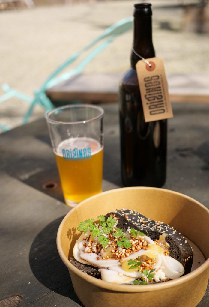 Bière à emporter et seiche roll avec pain à l'encre de seiche, gel de yuzu, céleri rémoulade et sarrasin soufflé