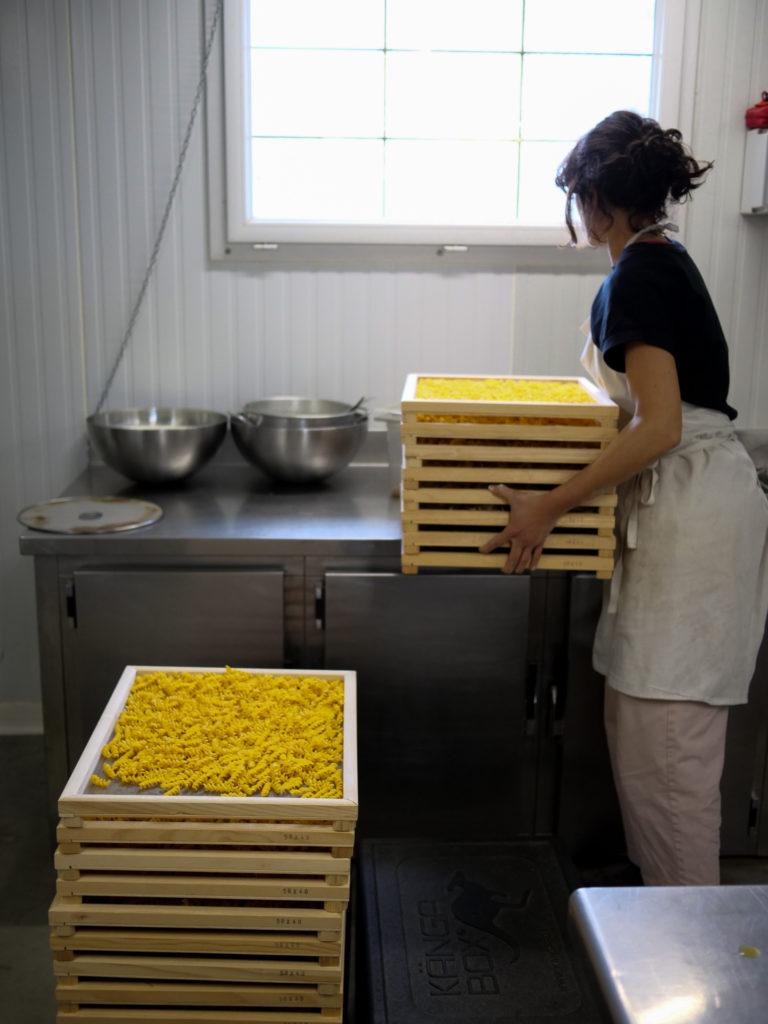 Madda entasse les plateaux de pâtes pour les faire sécher.